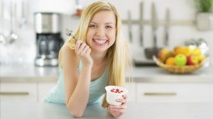 Happy-young-woman-eating-yogurt-in-kitchen